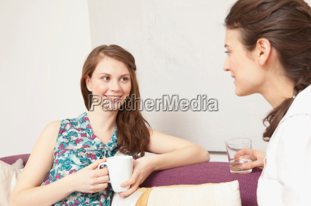 two women on a sofa chatting