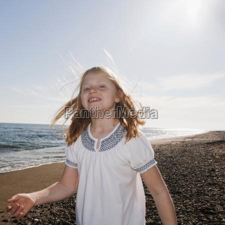 girl at beach smiling at camera