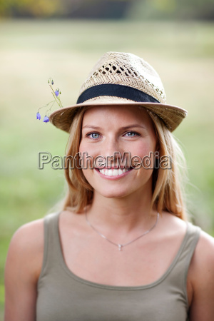 young woman wearing hat with flowers