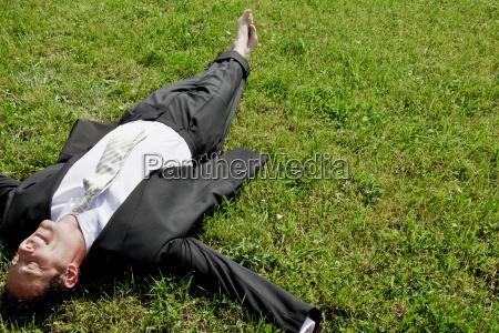 barefoot businessman lying on grass