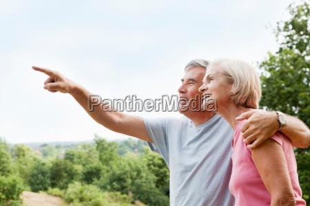 mature man embracing woman points away