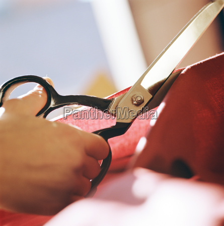 close up of woman cutting fabric
