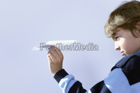 young boy playing with paper airplane
