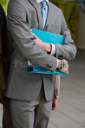 businessman carrying folder in courtyard