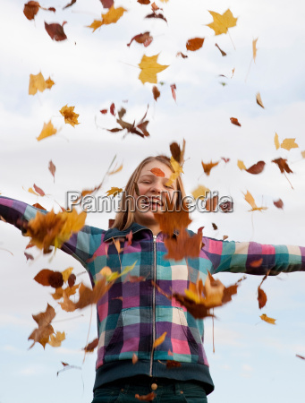 girl throwing autumn leaves into the