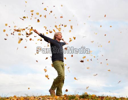 man walking through flying autumn leaves