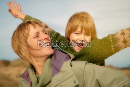 woman carrying young boy on beach