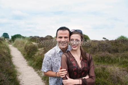 couple hugging on beach walkway