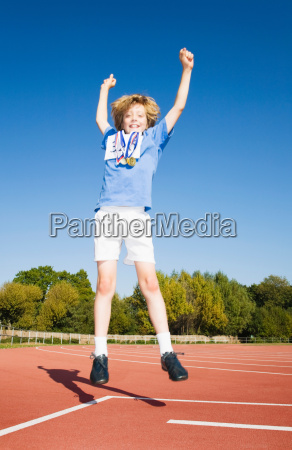 boy with medals jumping on race