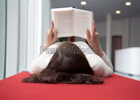 woman lying on her back reading