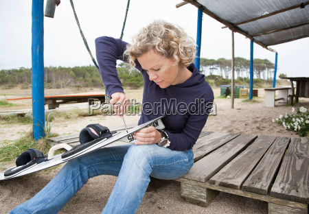 woman applying fin to her kiteboard