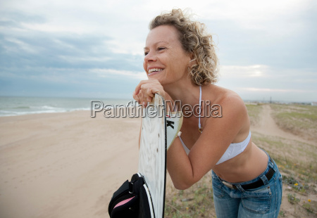 woman with kite board overlooking beach