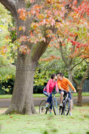 man and woman cycling in park
