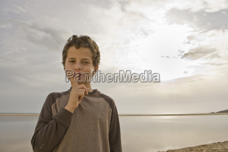 young boy with finger to lips