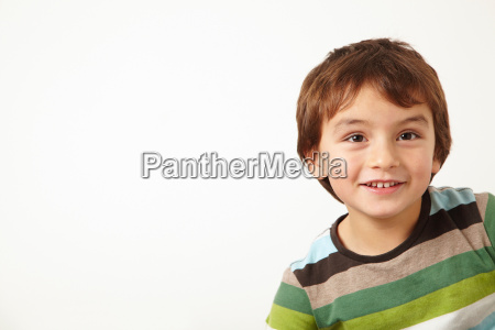 young boy smiling on white background