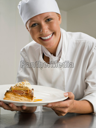 a female chef holding a pastry
