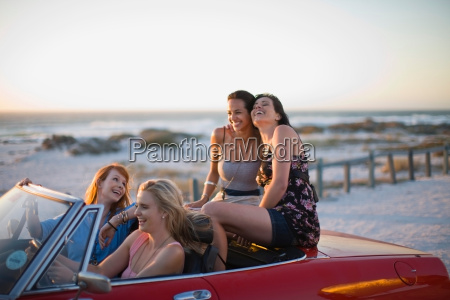 girls riding a red convertible car
