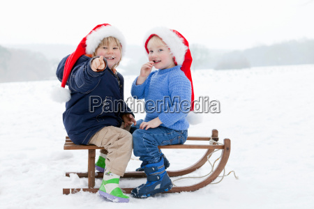two boys on a sledge wearing