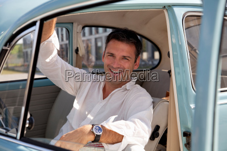 man looking through car window