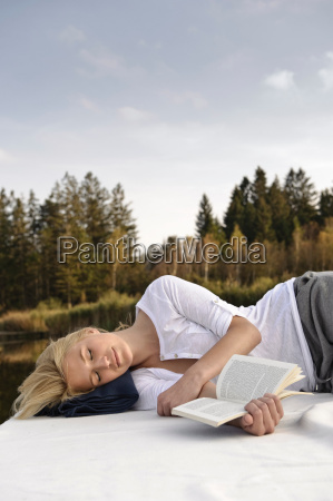 young woman lying on blanket reading