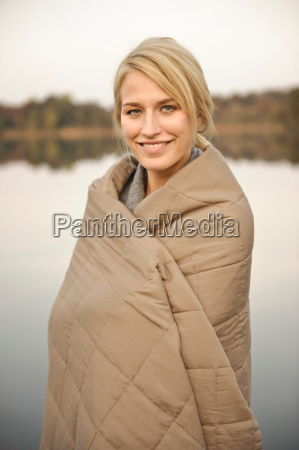 young woman wrapped in blanket smiling