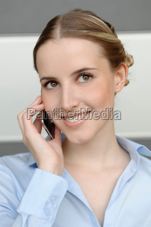 friendly woman using mobile in office