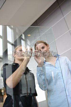 young businesswoman writing on glass
