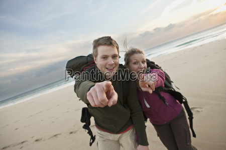backpacking couple pointing at camera