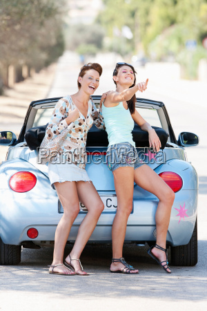two women laughing by a convertible