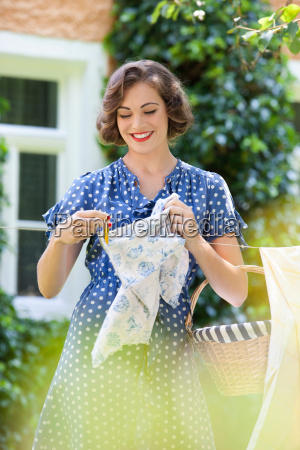 woman hanging towel on clothesline