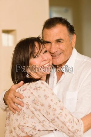 smiling older couple hugging