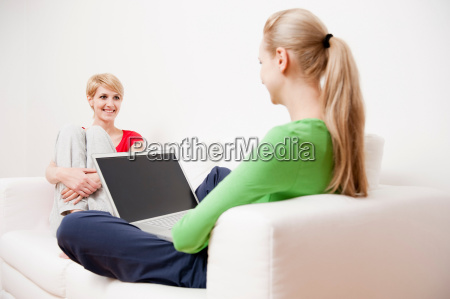 two women using laptop and phone