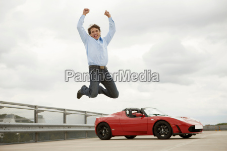 man jumping happily over electric car