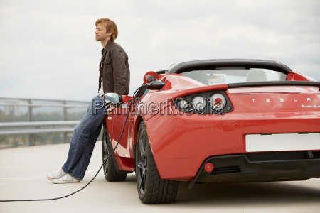 young man filling up his electric