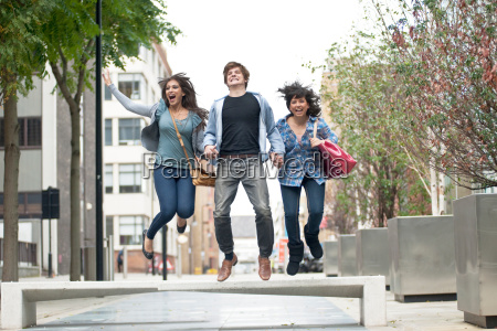 3 young people jumping in street