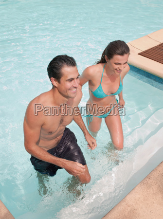 couple climbing out of swimming pool