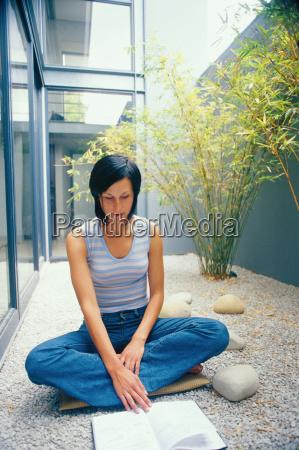 woman reading in courtyard garden