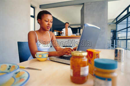 woman using laptop at breakfast table