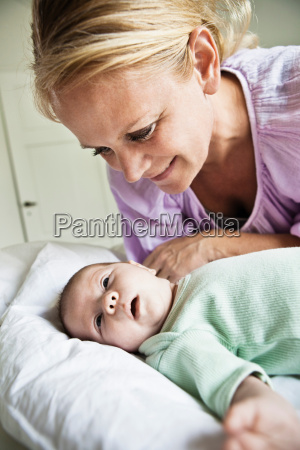 mother admiring infant on bed
