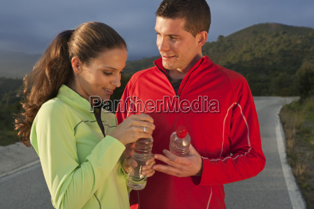 young couple holding water bottles