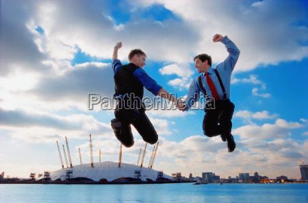 businessmen jumping against city skyline