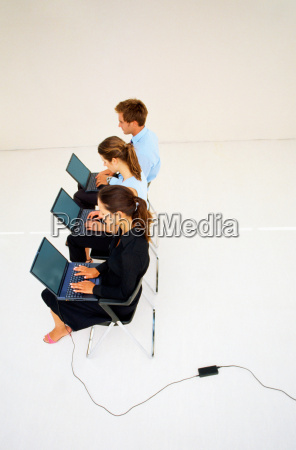 business people using laptops in office