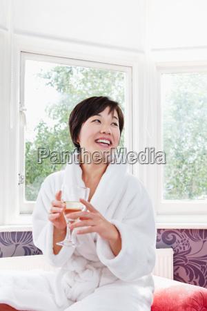 woman in bathrobe drinking glass of