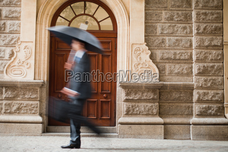 businessman carrying umbrella on street