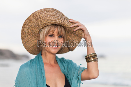 smiling woman wearing straw hat on