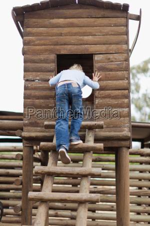 smiling boy climbing into playhouse