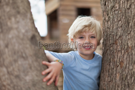boy playing in tree outdoors