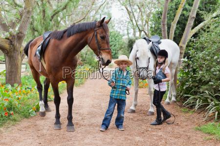 children walking horses in park