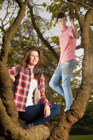 teenage couple climbing tree in park
