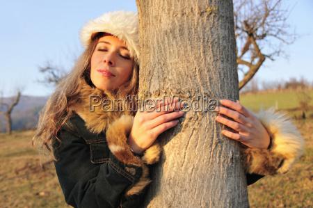 woman in fur hat hugging tree